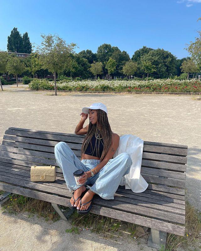 Foto de uma mulher em uma praça sentada em um banco de madeira. Ela usa uma regata cropped preta, calça jeans oversized, chinelo, boné branco e bolsinha. Ela olha para o lado e segura um copo de café na mão esquerda.