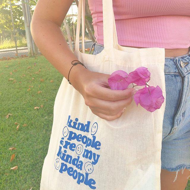 Foto do look de uma menina em um parque. Ela usa um top cropped rosa claro, shorts jeans, ecobag com estampa azul e segura uma flor na mão direita.