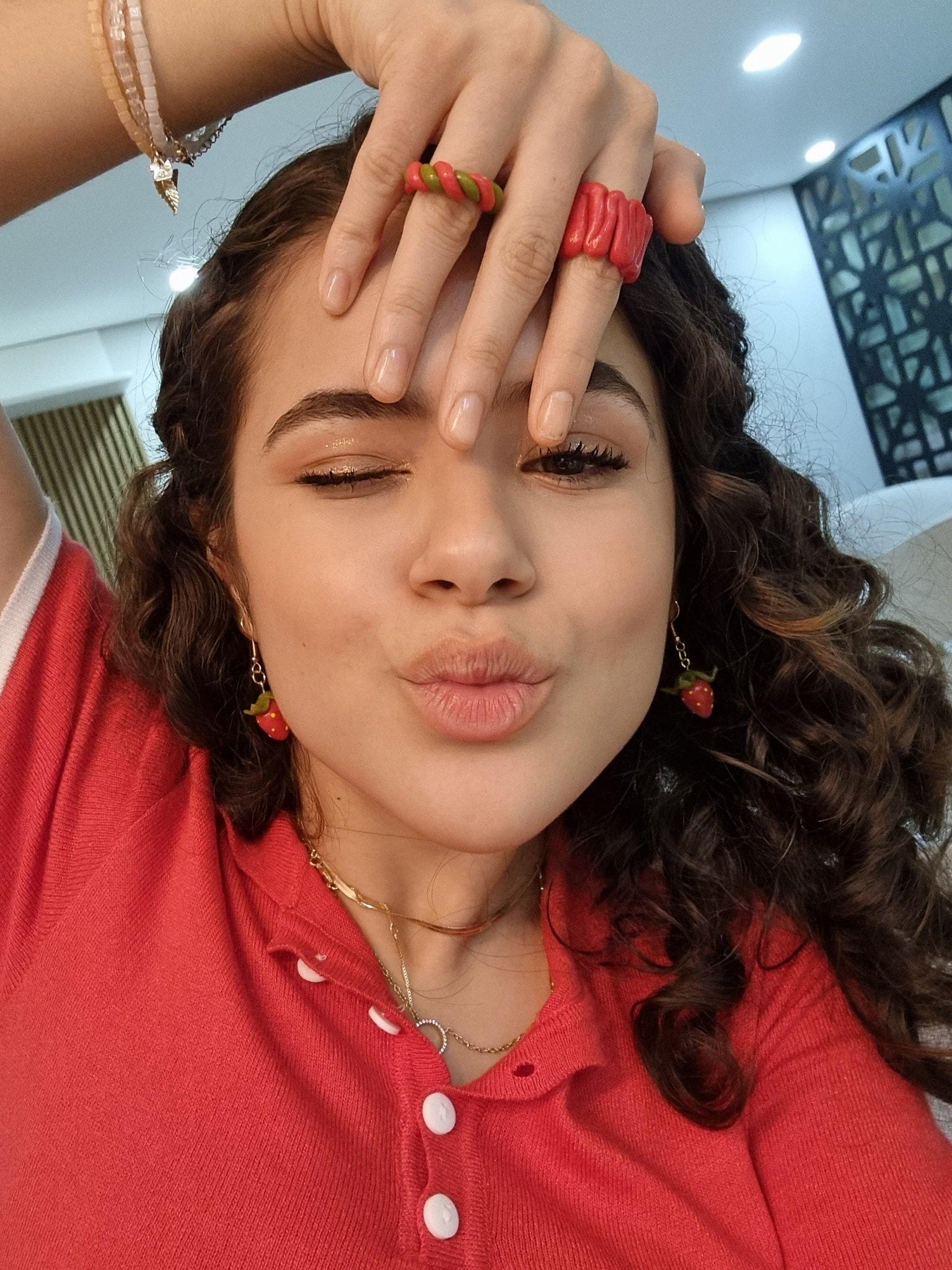 Maisa Silva com um dos olhos fechados, fazendo biquinho, usando blusa vermelha e uma das mãos na testa com anéis vermelhos nos dedos
