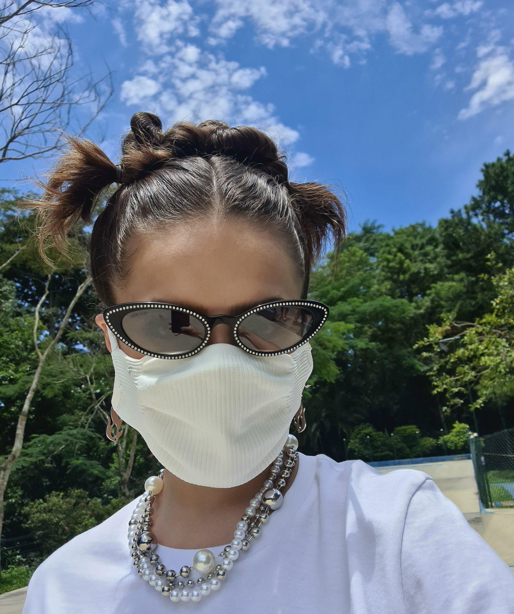 Maisa Silva usando óculos de sol e colar de pérolas, camiseta branca e máscara de proteção branca