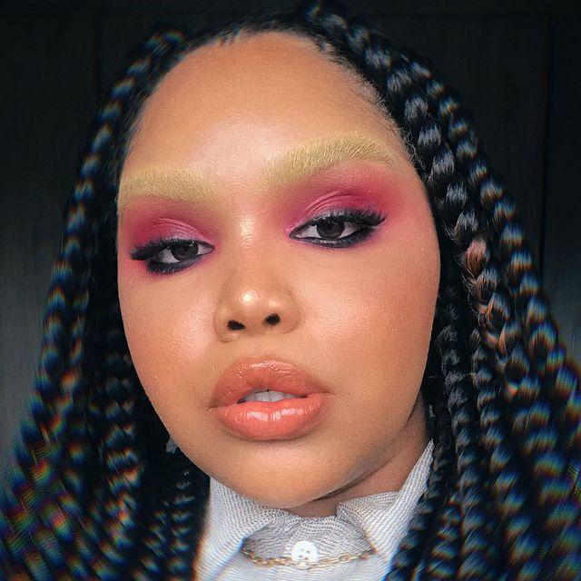 Selfie de uma mulher. Ela usa uma camisa, colar dourado, cabelo trançado solto e sua maquiagem é rosa com delineado preto, lápis de olho preto, pele natural, gloss e sobrancelha descolorida. Ela olha para a câmera e não sorri para a foto.