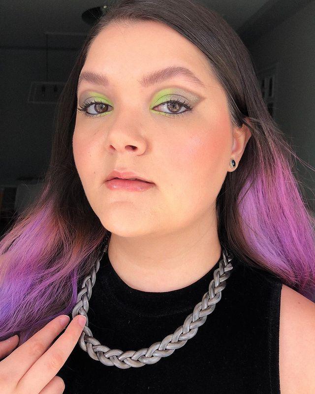 Selfie de uma mulher. Ela usa blusa preta de gola alta, corrente prata, cabelo solto e maquiagem com pele natural, gloss e olho com sombra verde e cinza metalizada com lápis de olho preto na linha d'água. Ela olha para a câmera e não sorri.