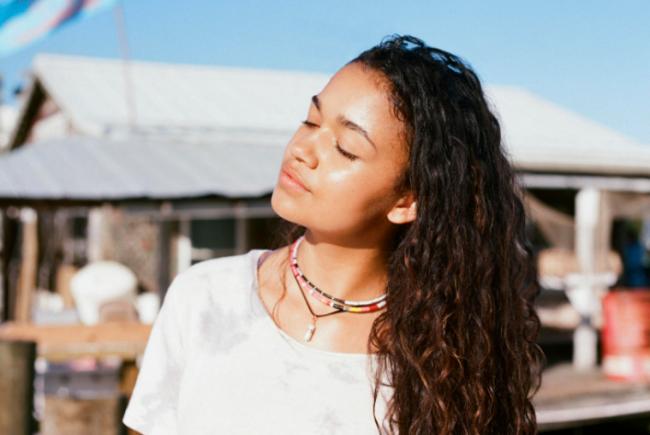 Kiara com a cabeça inclinada par ao lado direito, usando camisa branca e colares de miçanga.