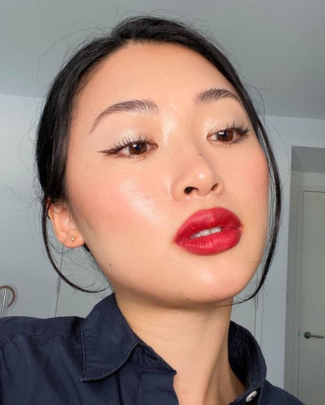 Selfie de uma mulher. Ela usa uma camisa preta, brinco pequeno, cabelo preso em um coque baixo e maquiagem glow com mini delineado gatinho e batom vermelho.