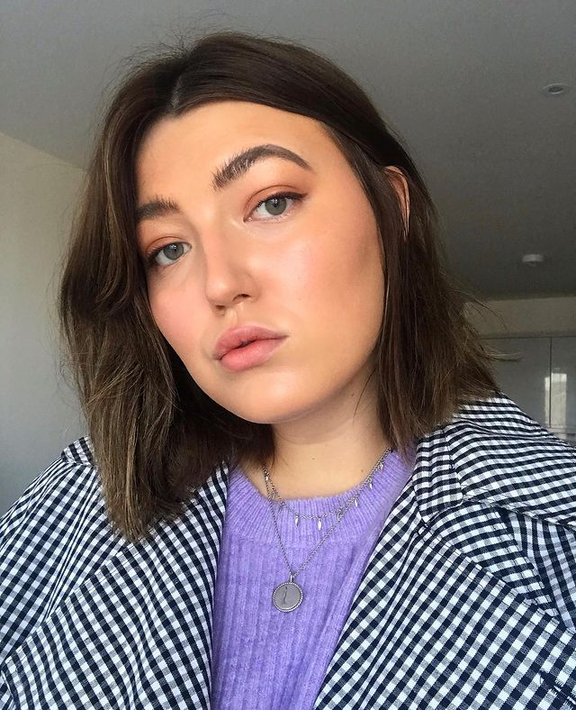 Selfie de uma mulher. Ela usa blusa lilás, casaco xadrez preto e branco como sobreposição, dois colares pratas, cabelo curto solto e maquiagem natural com mini delineado gatinho. Ela olha para a câmera e não sorri.