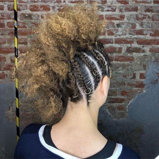 Penteado com moicano e tranças na lateral usando piercing.
