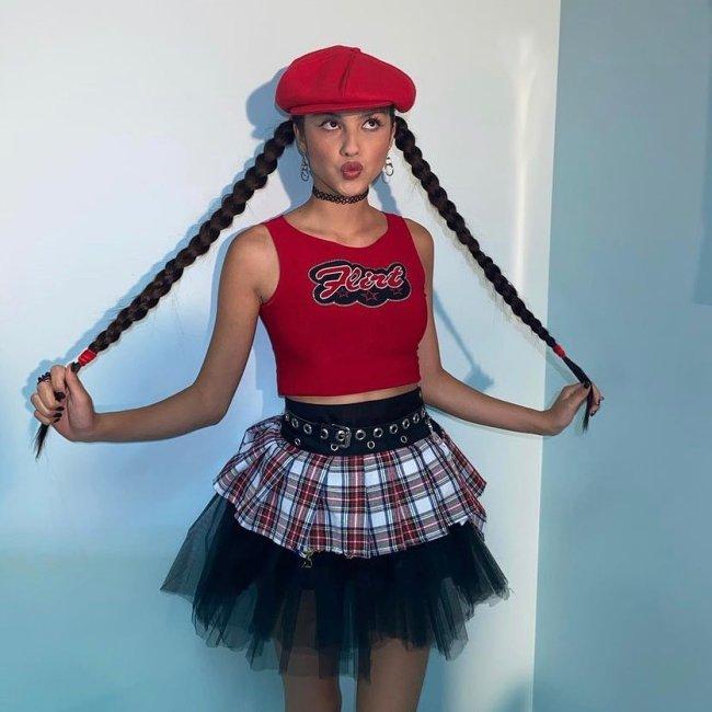 Olivia Rodrigo usando regata cropped vermelha, saia xadrez com tule preto e boina vermelha. Ela está com o cabelo preso em duas tranças laterais, fazendo bico e segurando as tranças com as duas mãos.