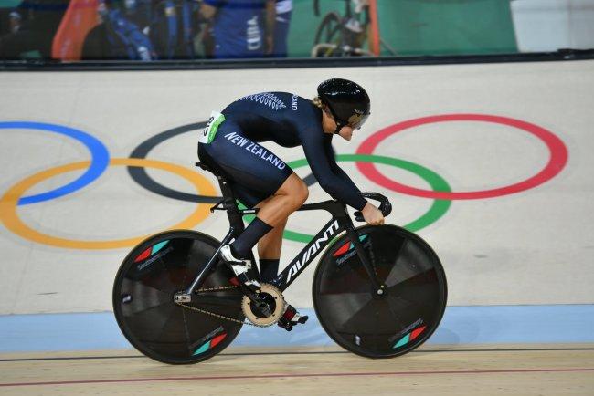 Ciclista durante competição olímpica; ela está em cima da bicicleta, em alta velocidade. O símbolo das Olimpíadas aparece ao fundo
