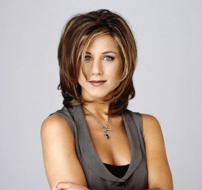 Personagem Rachel Green de Friends com os braços cruzados e com expressão sorridente.