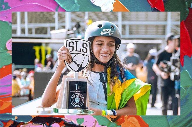 Foto da skatista Rayssa Leal vestindo um capacete, segurando a bandeira do Brasil e seu troféu de campeã nos EUA