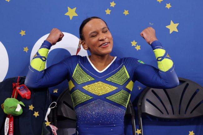 Rebeca Andrade celebrando conquista em Tóquio com os braços em muque. Ela veste um collant azul e amarelo.