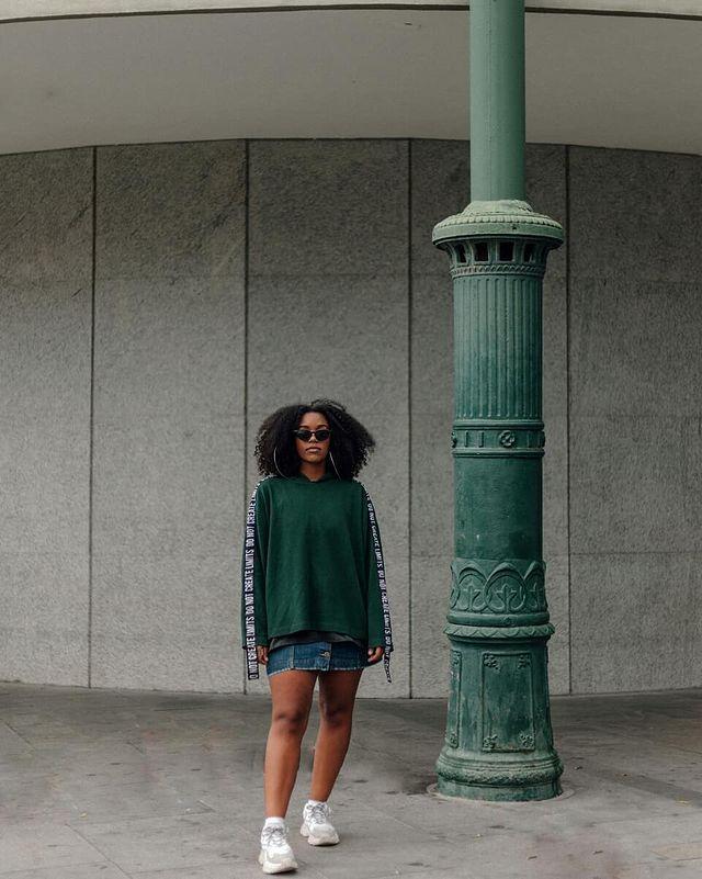 Jovem posando com moletom verde e saia jeans com tênis branco.