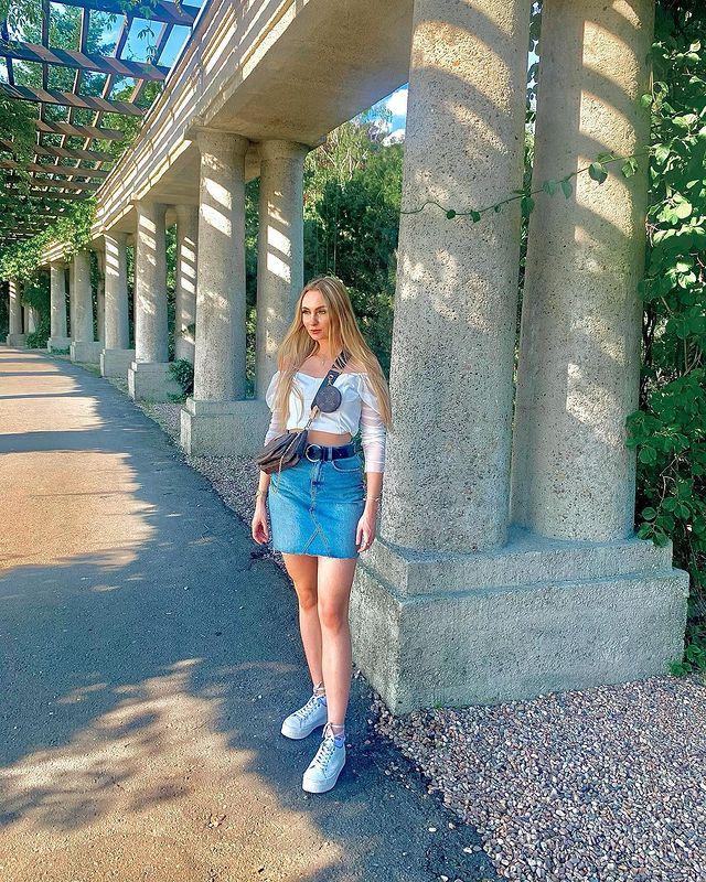 Jovem posando em frente a colunas, ela usa blusa branca e saia jeans com cinto.