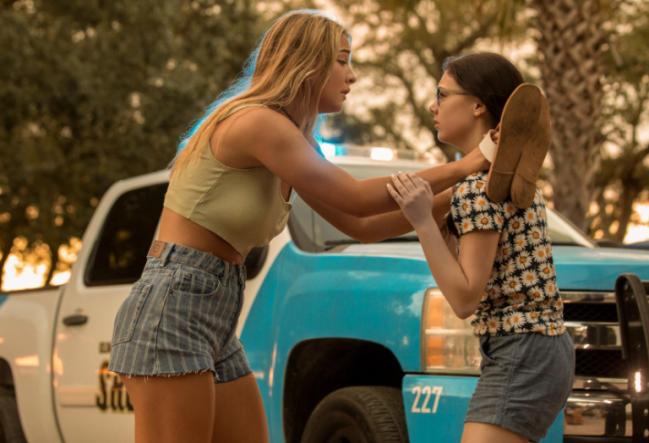 Sarah brigando com outra jovem, ela usa cropped verde e short listrado. Tem um carro de polícia atrás delas.