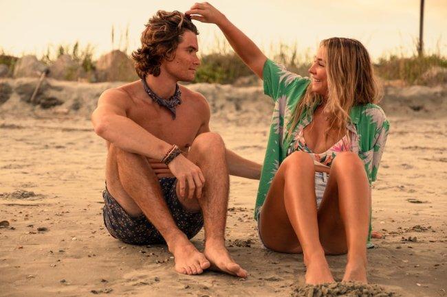 John B. e Sarah se olhando sentados na areia da praia. Ele está sem camisa e de short, e ela com camisa e biquíni.