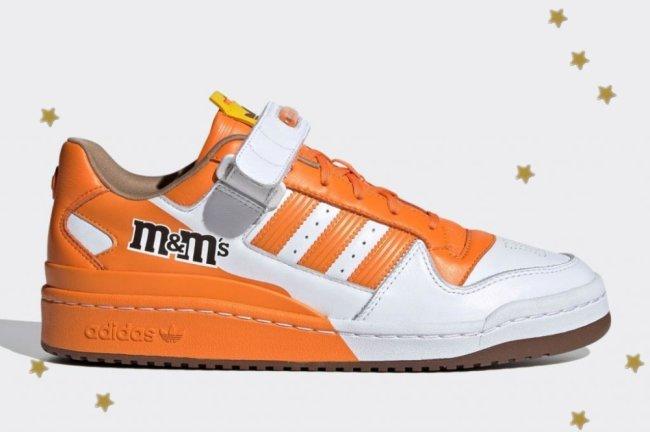 Tênis inspirado na marca M&M's, ele é laranja com detalhes em branco.