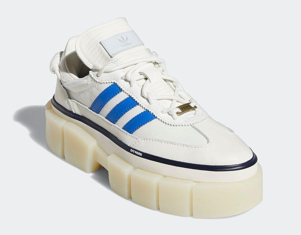 Tênis Super Sleek Chunky da coleção Adidas x IVY Park Rodeo. Ele é branco, com sola tratorada e listras azuis nas laterais.