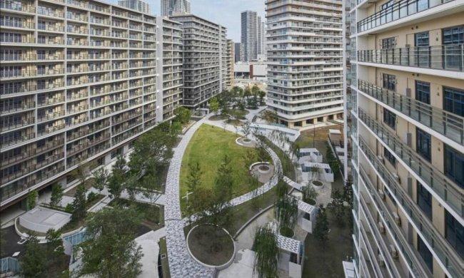 Imagem aérea da Vila Olímpicas de Tóquio 2020. Muitos prédios com uma praça no meio