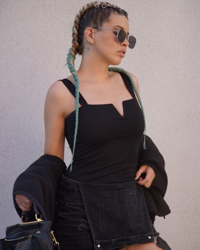Jovem com vestido preto com decote em v, usando óculos escuro e com expressão séria.