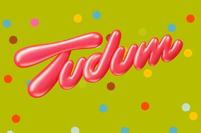 Logo do TUDUM escrito em letras garrafais rosa em um fundo verde com bolinhas coloridas