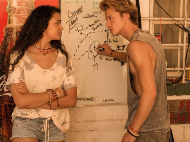Dois personagens de Outer Banks se olhando, enquanto um deles escreve na parede. A menina usa blusa branca com short jeans e o menino camisa sem manga com bermuda.