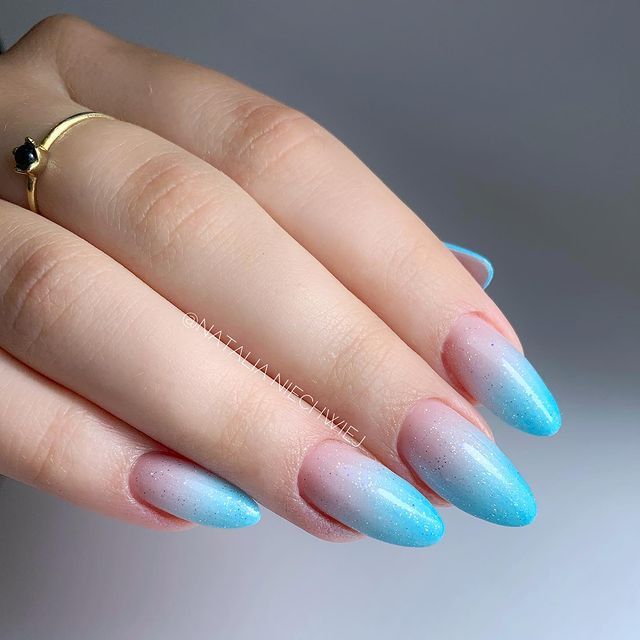 Foto de uma mão com foco nas unhas decoradas no estilo baby boomer em um tom de azul.