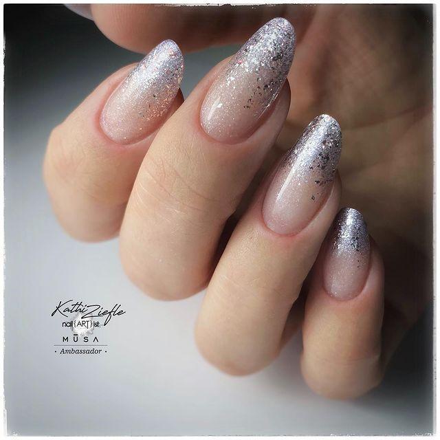 Foto de uma mão com foco nas unhas decoradas no estilo baby boomer com um glitter prata.