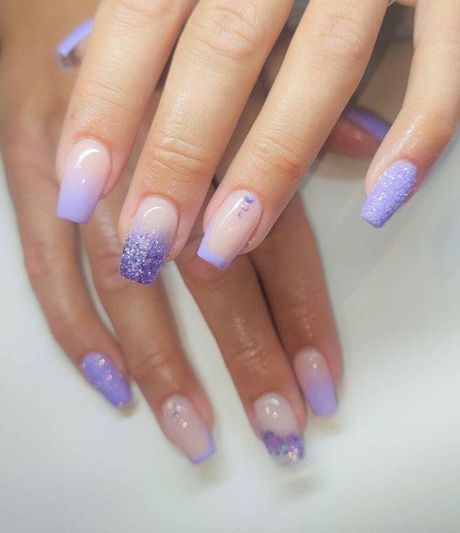 Foto de uma mão com close nas unhas decoradas no estilo baby boomer na cor lilás com detalhes de pedrinhas na unha do dedo anelar.