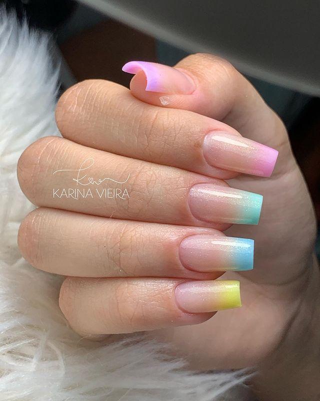 Foto de uma mão com foco nas unhas decoradas no estilo baby boomer nos tons de liás, rosa, azul claro, azul escuro e amarelo.
