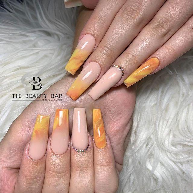 Foto de duas mãos com detalhe nas unhas decoradas no estilo baby boomer em um tom de nude e laranja.
