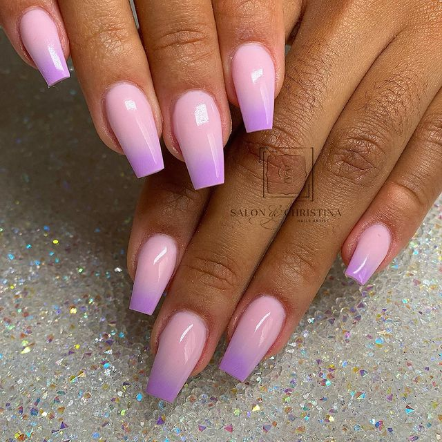 Foto de duas mãos com foco nas unhas decoradas no estilo baby boomer nos tons rosa e lilás.