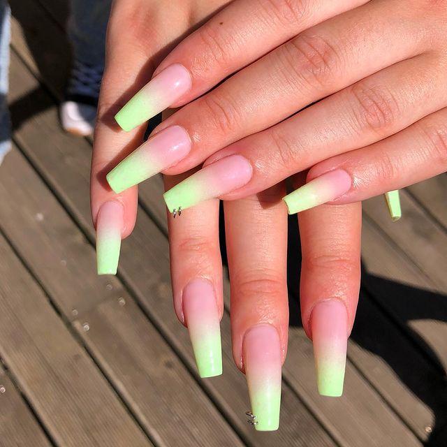 Foto de duas mãos com foco nas unhas decoradas no estilo baby boomer em um tom de verde claro e detalhe de mini argolas nas unhas dos dedos anelares,