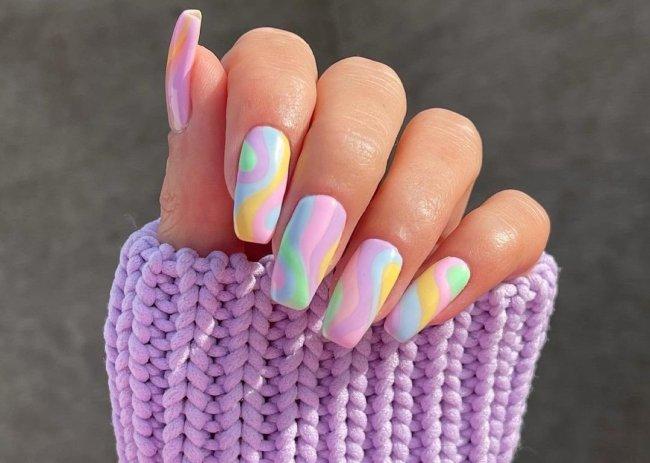 Foto com close nas unhas com esmaltes coloridos em diversas cores.