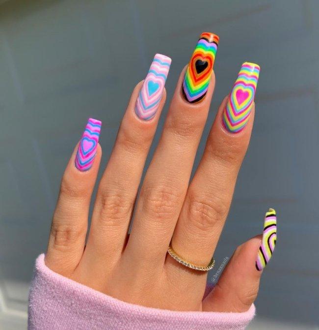 Foto com foco nas unhas exibindo a nail art chamada bubble heart, que traz vários corações um dentro do outro.
