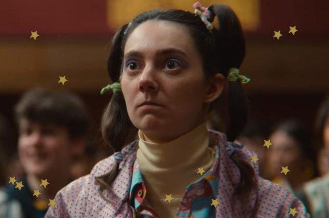 Bubble Hair, em personagem de Sex Education. Com pompons coloridos e a personagem aparecem com expressão séria.