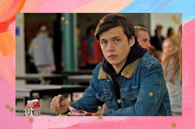 Jovem sentado em refeitório com expressão séria. Ele usa jaqueta jeans.