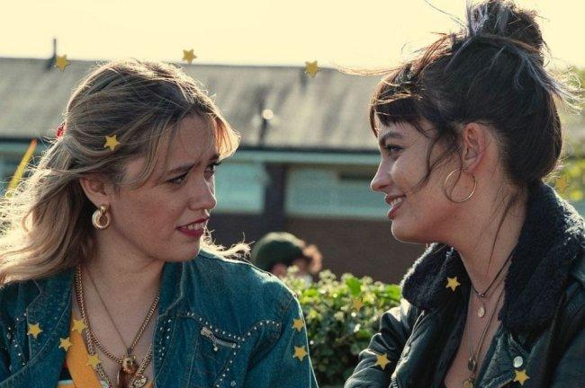 Personagens de Sex Education se olhando com expressão sorridente. As duas estão de lado para a câmera.