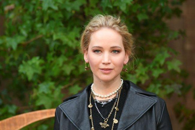 Jennier Lawrence vestida com um look total black sobre um fundo de árvores, cheia de colares e olhando serena para a câmera