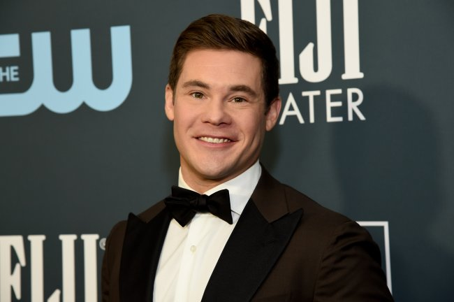 Adam Devine no Critics' Choice Awards em 2020; ele usa um terno preto com gravata borboleta preta e camisa branca; ele está posando e sorrindo para a câmera no tapete vermelho da premiação; a imagem mostra apenas do peito para cima do ator