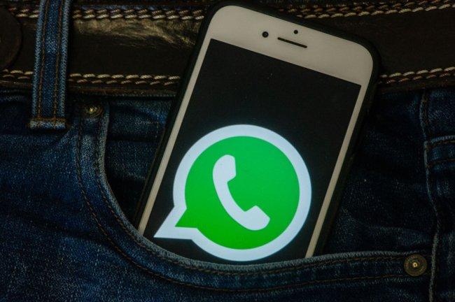 Foto de um iphone no bolso de uma calça jeans. Na tela, aparece o logo do WhatsApp