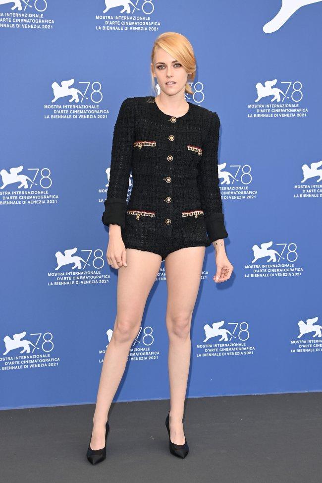 Kristen Stewart no evento de Spencer, no Festival de Cinema de Veneza. Ela está usando um macaquinho preto com detalhes em dourado e um sapato preto.
