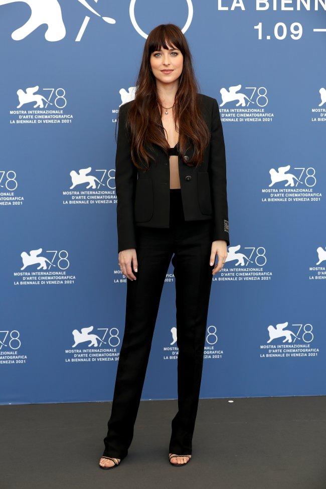 Dakota Johnson no Festival de Cinema de Veneza. Ela está usando um terninho todo preto e uma sandália preta. O blazer está desabotoado e dá para ver uma parte de sua lingerie preta.
