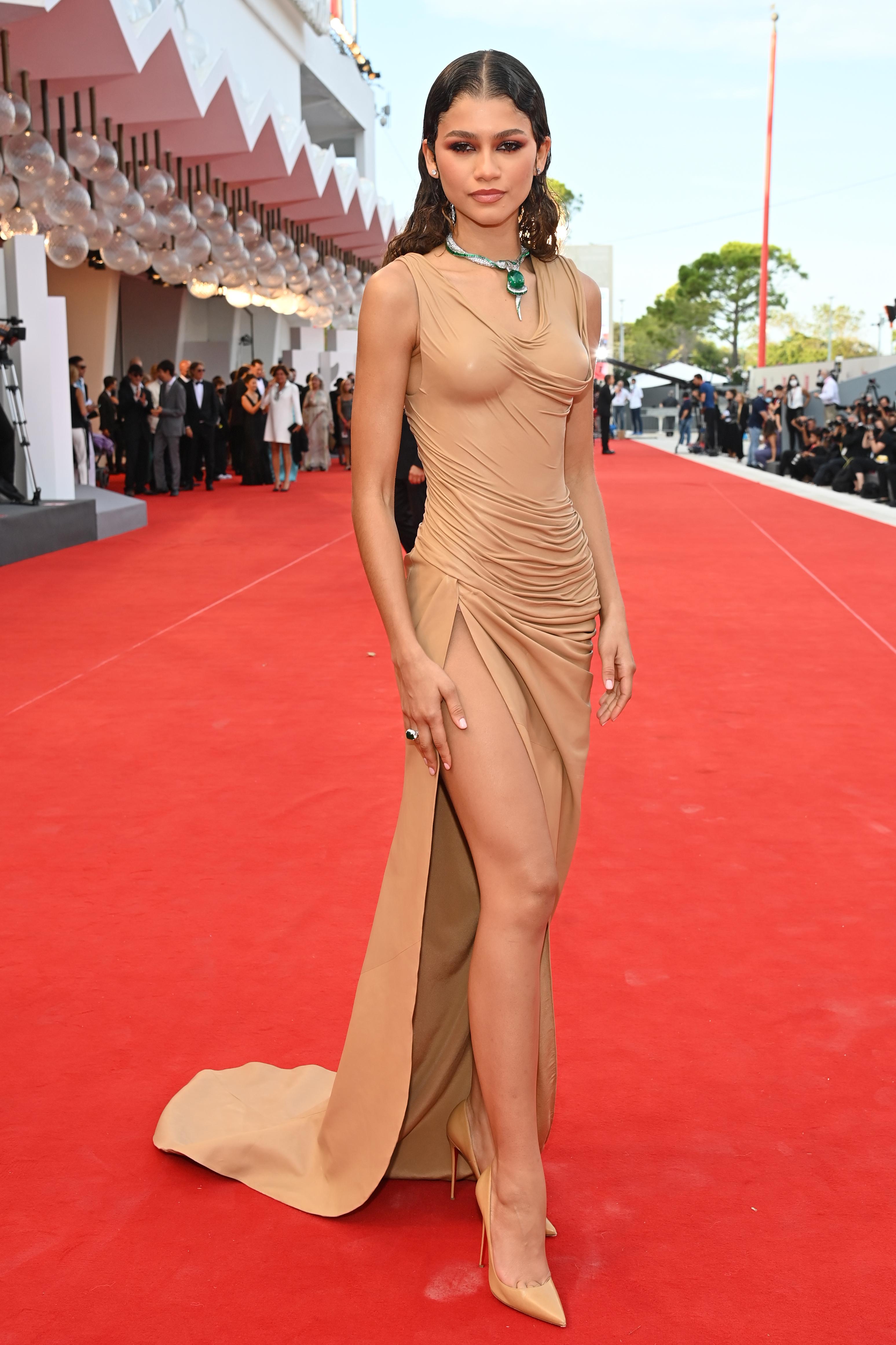 Zendaya no tapete vermelho de Duna, no Festival de Cinema de Veneza. Ela está usando um vestido nude com fenda lateral e colar prata com pedra esmeralda.