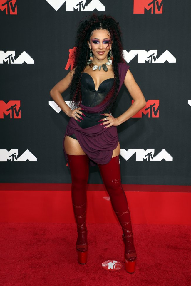 Foto da Doja Cat no tapete vermelho do MTV Video Music Awards 2021. Ela usa um corset macacão preto com detalhe de tecido roxo na cintura, bota vermelha, cabelo meio preso e maquiagem com sombra roxa. Ela está com as mãos na cintura, olha para a câmera e sorri levemente.
