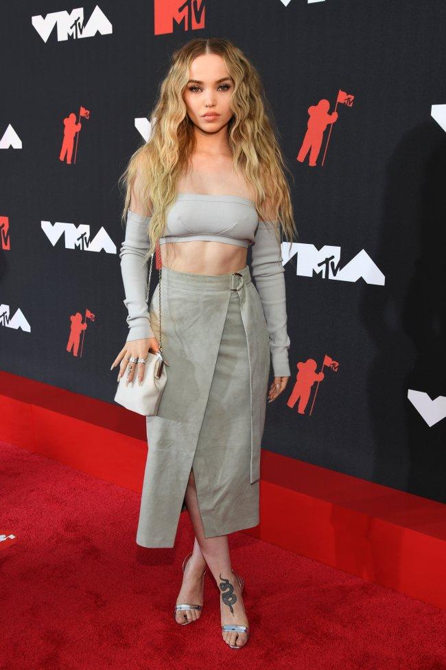 Foto da Dove Cameron no tapete vermelho do MTV Video Music Awards 2021. Ela usa um top cropped cinza com manga, saia midi cinza com fenda, sandália de salto na cor prata, bolsa branca, cabelo solto e maquiagem básica. Ela olha para a câmera e não sorri.