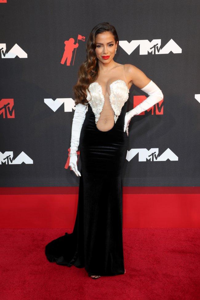 Foto da Anitta no tapete vermelho do MTV Video Music Awards 2021. Ela usa um vestido preto com detalhe branco no decote, luvas de ópera brancas, cabelo solto e maquiagem com batom vermelho. Ela está com a mão esquerda na cintura, olha para a câmera e sorri levemente.