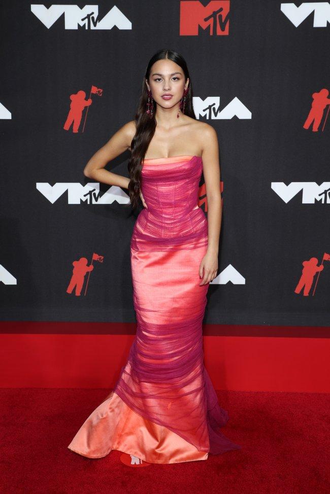 Foto da Olivia Rodrigo no tapete vermelho do MTV Video Music Awards 2021. Ela usa um vestido longo rosa, cabelo solto, brinco rosa e maquiagem básica. Ela olha para a câmera e não sorri.