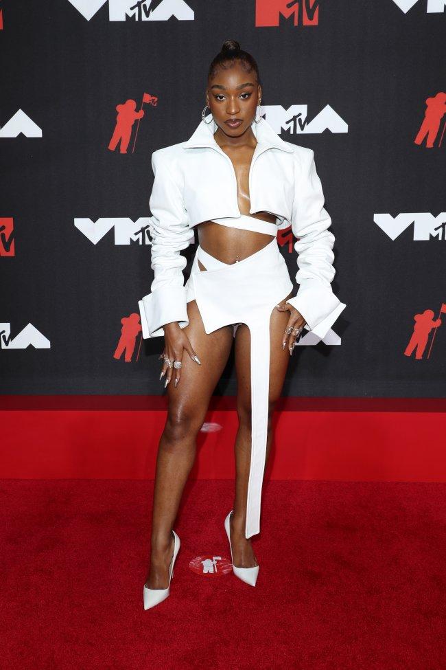 Foto da Normani no tapete vermelho do MTV Video Music Awards 2021. Ela usa um conjunto de cropped e shorts branco com recortes, salto branco, cabelo preso em um rabo de cavalo e maquiagem com delineado. Ela olha para a câmera e não sorri