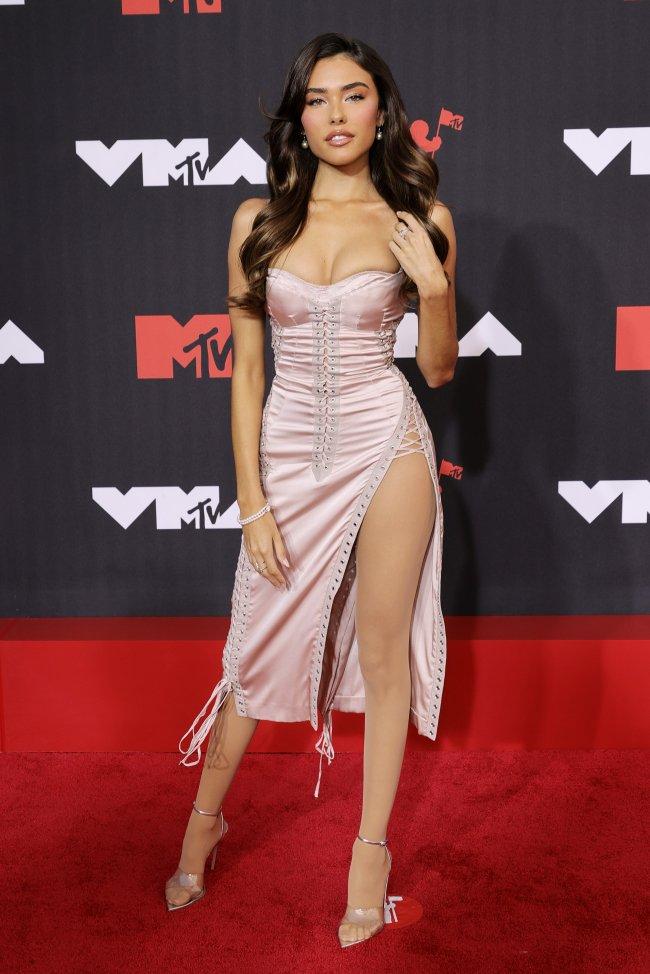 Foto da Madison Beer no tapete vermelho do MTV Video Music Awards 2021. Ela usa um vestido rosa com fenda na perna, salto fino, cabelo solto e maquiagem básica. Ela olha para a câmera e sorri levemente.