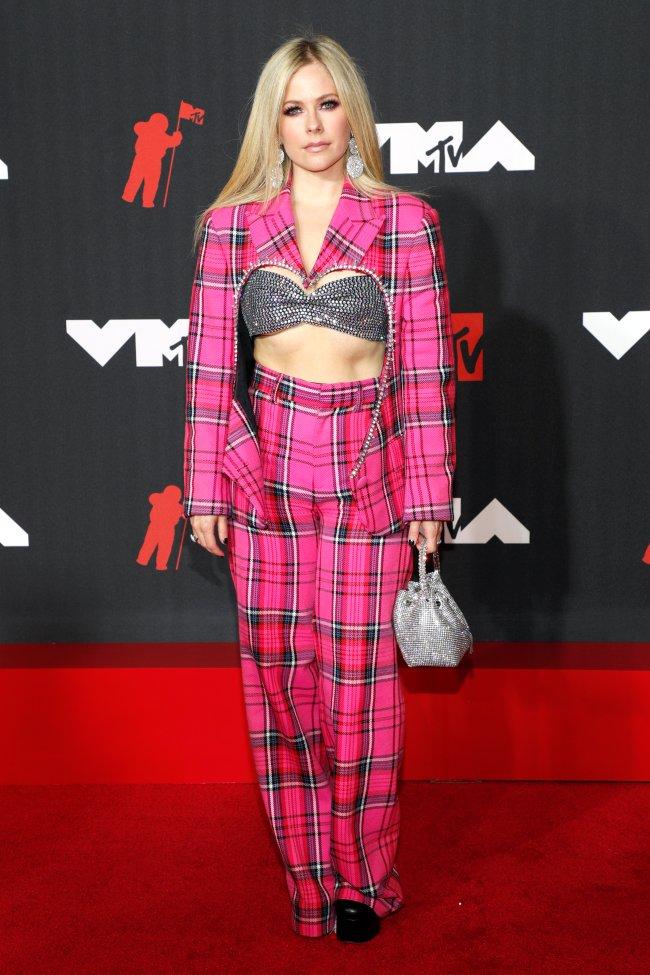 Foto da Avril Lavigne no tapete vermelho do MTV Video Music Awards 2021. Ela um um conjuntinho rosa com casaco e calça rosa xadrez e top de brilho, bolsa de brilho, cabelo solto e maquiagem com sombra preta. Ela olha para a câmera e não sorri.